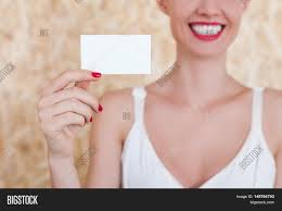 smiling holding a blank business card in her hand with red