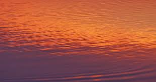 orange color sunset reflects in calm lake water with golden
