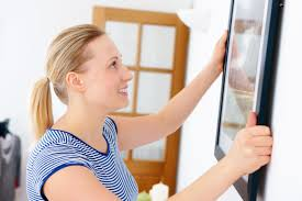 interior designers and decorating angie s list woman handing painting as part of interior design