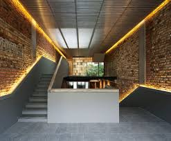 exposed brick wall lighting the pool shophouse by farm and kd architects to live in