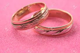 pink wedding rings images Gold wedding rings without stones on a pink background stock photo jpg