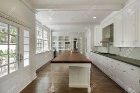 luxury white kitchen with large island and cabinets stock photo