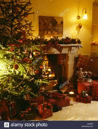 decorated christmas tree beside fireplace with lighted candles and