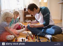 father painting daughters toenails with fingernail polish stock