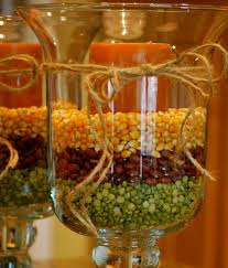 fall decorating with hurricane vases using yellow popping corn