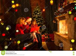 happy family reading book at home by fireplace in warm and cozy