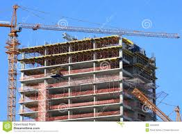 crane and high rise building under construction against blue sky