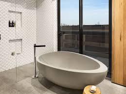 interior oval white acrylic freestanding bathtub on brown tile