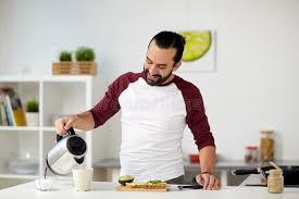 cuisiner avec une bouilloire homme avec la bouilloire faisant le thé pour le petit déjeuner à la