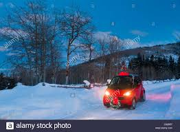 person driving a red smart car at dusk with a small decorated