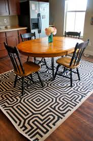 small dining room using black white geometric rug under dining