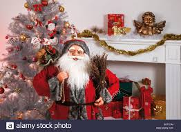 santa claus decorated christmas tree in front a fireplace with
