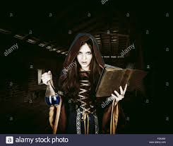 beautiful young halloween witch wearing vintage gothic dress with