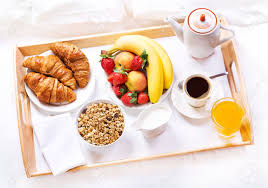 breakfast in bed tray with coffee croissants cereals and fruits