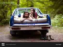 couple laying on air mattress in truck bed stock photo offset