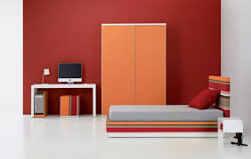 bright teen room design with red wall paint oraange cabinet desk