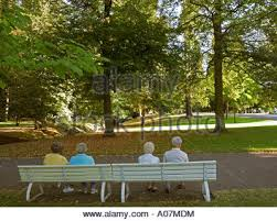 Benches In Park - a group of pensioners sitting on park benches in gijon spain stock
