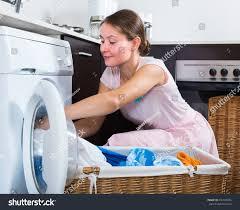 portrait cheerful housewife loading washing machine stock photo