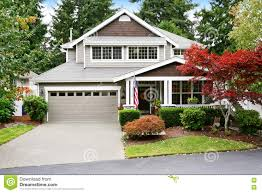 nice curb appeal of grey house with covered porch and garage stock