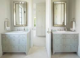 cream washstand with ornate cabinet doors and honed gray and white