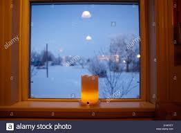 candle in the window looking out snow covered in small