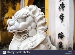 marble lions side view of an ornately carved white marble lions guard the