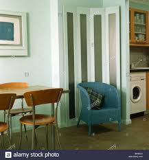 Modern Studio Furniture by Blue Tub Chair In Front Of Folding Screen In Corner Of Modern