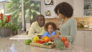 african american family chopping vegetables in kitchen stock