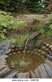 ornamental garden pond water feature with earthenware jug and