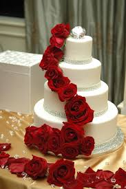 cascading red roses on a fantastic wedding cake we are in love
