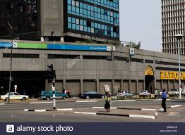 people walk across a street in front of standard chartered bank in