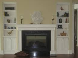 white wooden shelf cabinet flanking white cement mantel fireplace
