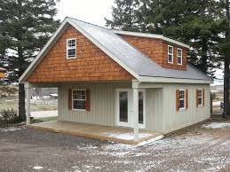 small cabin with porch metal roof shingled dormer wood shutters