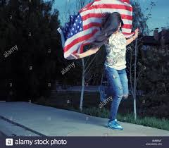beautiful young woman with american flag dancing outdoors