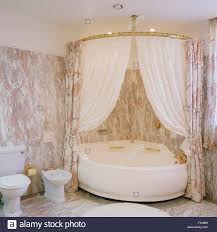 white shower curtains on corner bath in an eighties marble