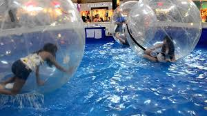 asian inside large plastic balls while floating on water