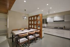 view of kitchen and dining space diving through a wooden partition