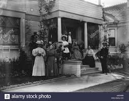 1890s 1900s family posing for photograph outside front porch of