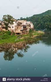 Landscape With Houses by Tranquil River With Houses Along The Water U0027s Edge In A Small