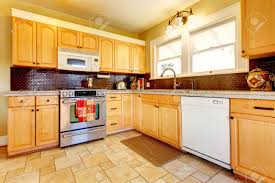 yellow kitchen with wood cabinets and dark brown backsplash design
