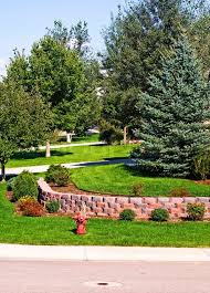 well manicured yard with a retaining wall on a corner lot located