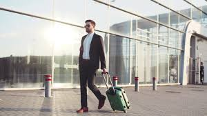 stylish young bearded man talking on the phone while entering the stylish young bearded man in sunglasses exiting the airport terminal with luggage answers the phone