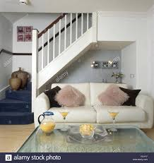 fluffy cushions on white sofa beside staircase in economy style