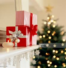 gift boxes on mantelpiece with christmas tree in background stock