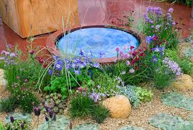 Rock Garden With Water Feature Tiny Water Feature In Garden Of Flowers Plant Flower Stock