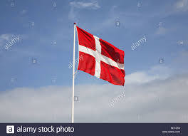 the danish flag dannebrog against white clouds and a blue sky