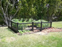 diy small raised vegetable garden along black wood and wire fence