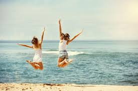 travel girls images Two happy girls jumps at sunny beach stock photo image of female jpg