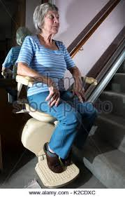 elderly woman using stairlift stair glider mechanical device