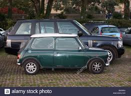 mini range rover a small mini car parked next to a big range rover 4x4 car in a car